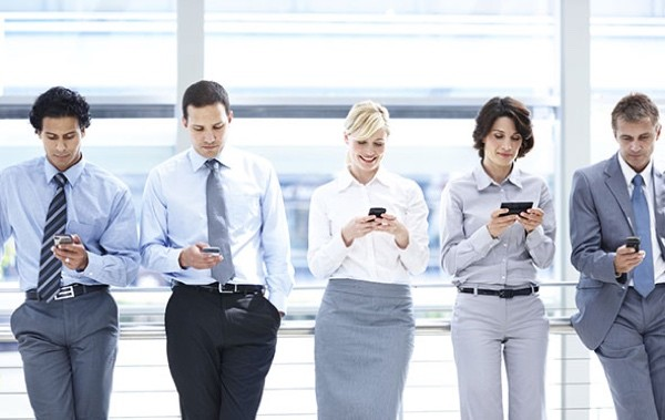 A group of executives standing in line and looking at their smartphones